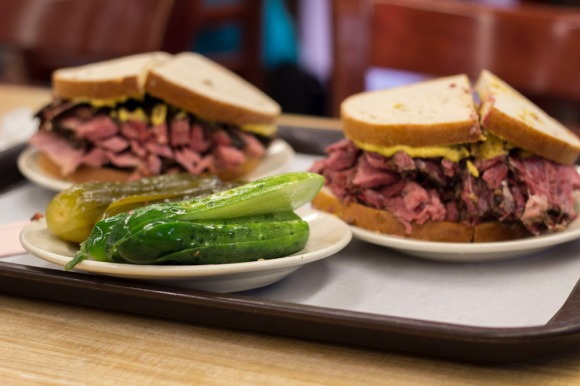 A plate of pickles, a pastrami on rye, and a corned beef on rye at Katz's Delicatessen
