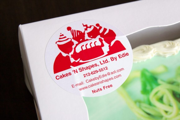 A sticker on a Cakes 'N Shapes cake box